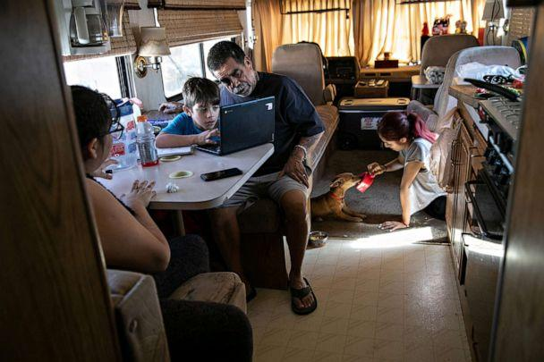 PHOTO: Hector Medrano helps his son Angel, 8, with distance learning while in their RV on Oct. 09, 2020, in Phoenix. (John Moore/Getty Images)