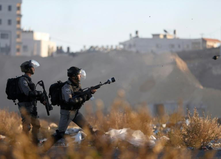 Israeli troops take position during clashes with Palestinian protesters near an Israeli checkpoint in the West Bank city of Ramallah on December 8, 2017