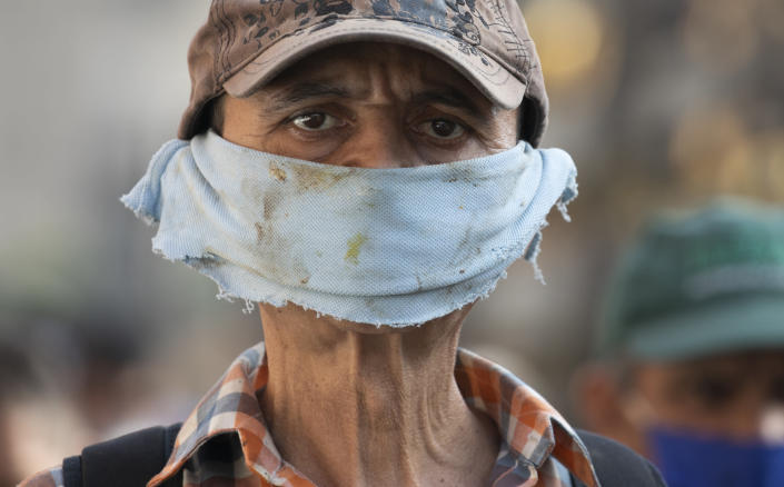 A man wears a piece of cloth as a face mask amid the spread of the new coronavirus at a street market in Caracas, Venezuela, Friday, April 10, 2020. (AP Photo/Ariana Cubillos)