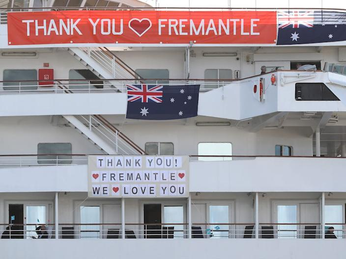 "The MV Artania is seen with ""Thank You Fremantle"" banners and Australian flags at the Fremantle Passenger Terminal in Australia on March 28, 2020."