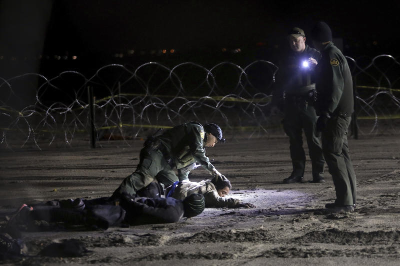 A U.S. Border Patrol agent pats down Honduran migrants after they crossed onto U.S territory from Tijuana, Mexico, on Friday, Nov. 30, 2018. Thousands of migrants who traveled via a caravan want to seek asylum in the U.S., but inspectors at the San Ysidro border crossing are processing about 100 claims a day, meaning they will likely have to wait weeks or months. (AP Photo/Felix Marquez)