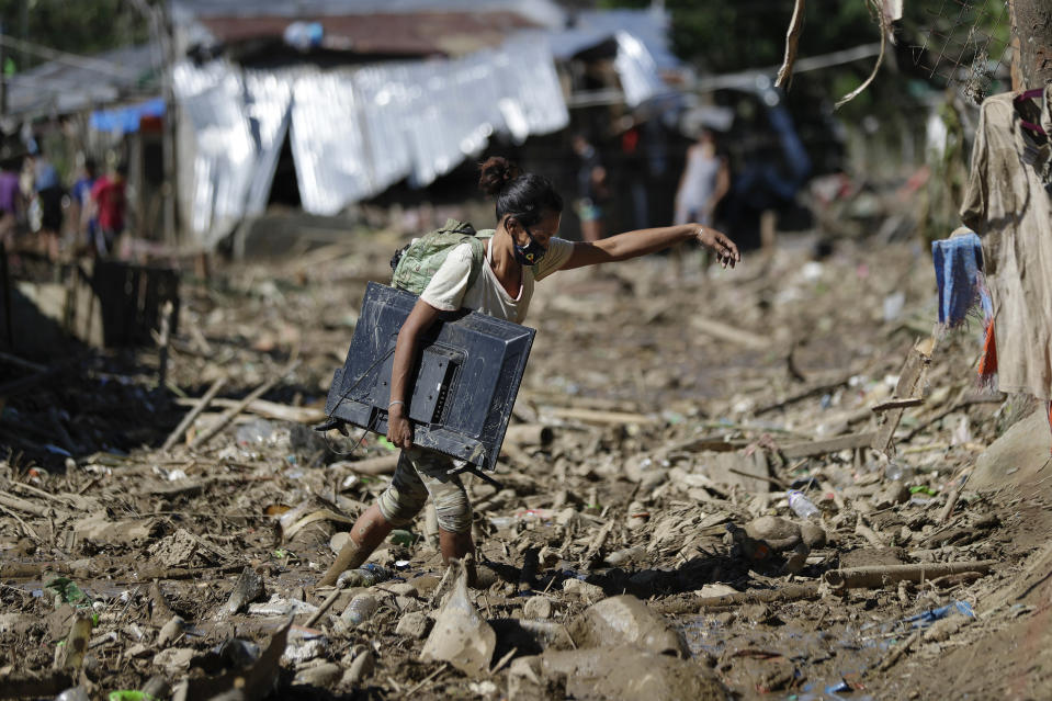 A woman carries a computer monitor she retrieved from her house at the typhoon-damaged Kasiglahan village in Rodriguez, Rizal province, Philippines, Friday, Nov. 13, 2020. Thick mud and debris coated many villages around the Philippine capital Friday after Typhoon Vamco caused extensive flooding that sent residents fleeing to their roofs and killing dozens of people. (AP Photo/Aaron Favila)