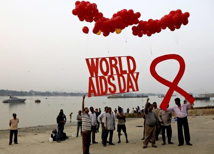 Activists prepare to release campaign materials on air ahed of World AIDS Day on the banks of Ganges River in Kolkata, India, Wednesday, Nov. 30, 2016. World AIDS Day is celebrated on Dec. 1 every year to raise awareness about HIV/AIDS and to demonstrate international solidarity in the face of the pandemic. (AP Photo/Bikas Das)