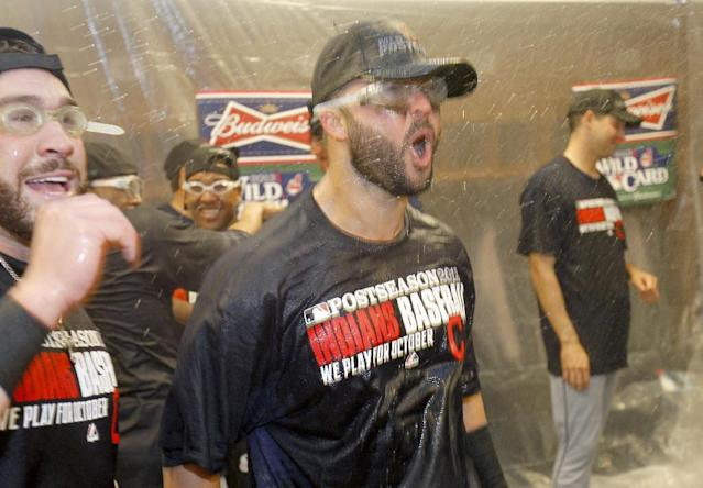 Cleveland Indians first baseman Nick Swisher, center, is showered with champagne with teammates in the locker room after the Indians beat the Twins 5-1 in a baseball game in Minneapolis, Sunday, Sept. 29, 2013, to clinch a wild card spot in the playoffs. (AP Photo/Ann Heisenfel