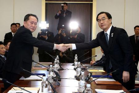 Head of the North Korean delegation, Ri Son Gwon shakes hands with South Korean counterpart Cho Myoung-gyon as they exchange documents after their meeting at the truce village of Panmunjom in the demilitarised zone separating the two Koreas, South Korea, January 9, 2018.  REUTERS/Korea Pool
