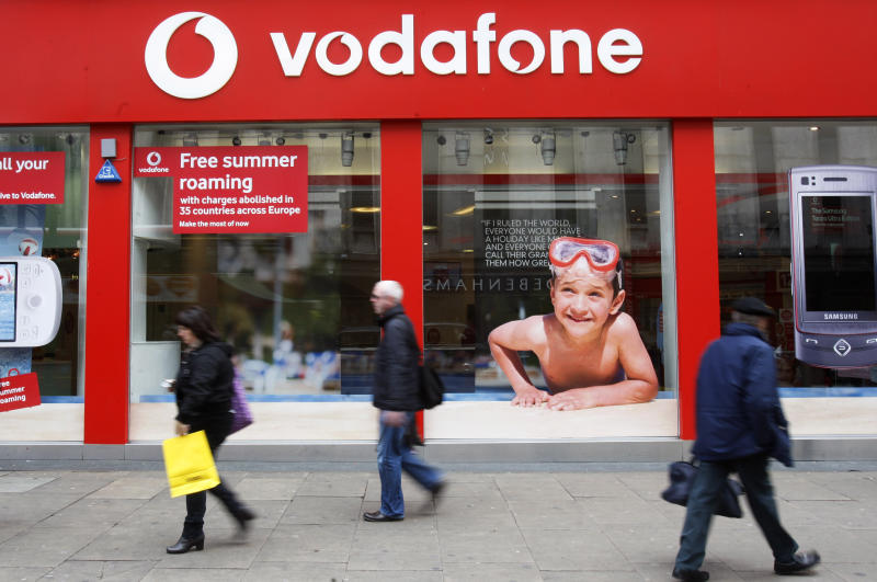FILE - In this Tuesday, May 19, 2009, file photo, people walk by a branch of Vodafone in central London. Verizon says, Monday, Sept. 2, 2013, it has agreed to buy Vodafone's stake in Verizon Wireless for $130 billion. (AP Photo/Sang Tan, File)