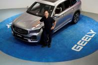 Zhejiang Geely Holding Group's Chairman Li Shufu poses for pictures next to a Xingyue L SUV at Geely headquarters in Hangzhou