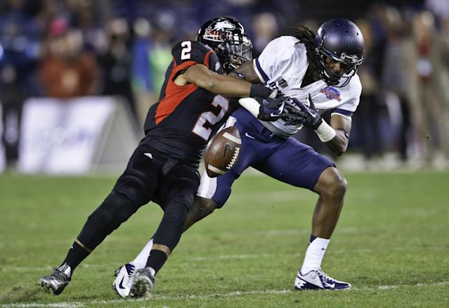 Northern Illinois cornerback Sean Evans strips away the ball from Utah State receiver Ronald Butler after a catch during the first half of the Poinsettia Bowl NCAA college football game Thursday, Dec. 26, 2013, in San Diego. Utah State recovered the fumble. (AP Photo/Lenny Ignelzi)