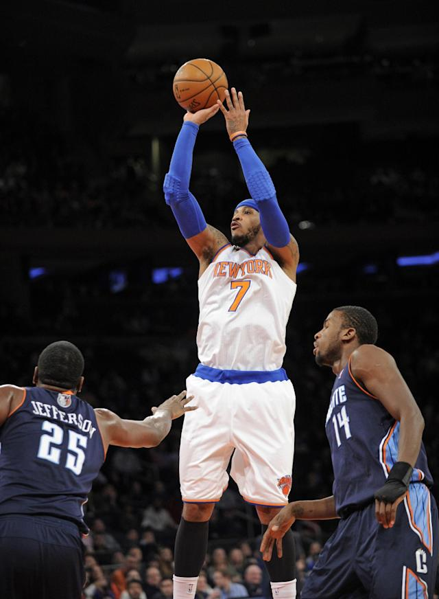 New York Knicks' Carmelo Anthony (7) puts up a shot between Charlotte Bobcats' Al Jefferson, left, and Michael Kidd-Gilchrist, right, during the first quarter of an NBA basketball game, Friday, Jan. 24, 2014, at Madison Square Garden in New York. Anthony scored 62 points as the Knicks defeated the Bobcats 125-96. (AP Photo/Bill Kostroun)
