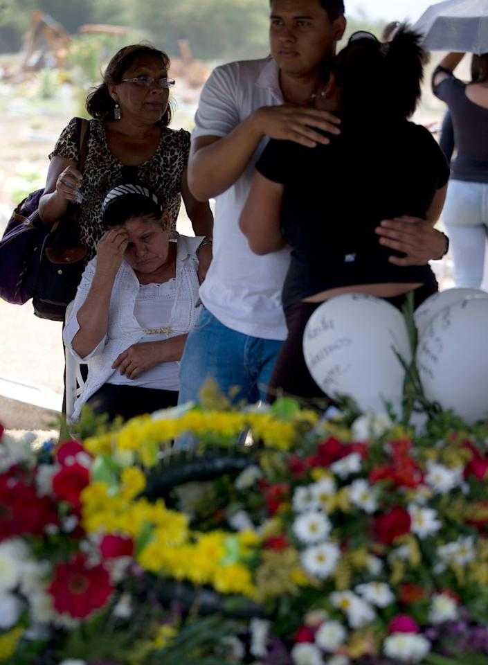 In this photo taken on Friday, March 14, 2014. Relatives of University student Jesus Enrique Acosta cry next to his tomb during his funeral grave in Valencia, Venezuela. The people of the poor district of La Isabelica were made to pay for taking to the streets in anti-government protests. More than a dozen masked men on motorcycles roared through, shooting up a barricade and killing a university student and a 42-year-old man painting his house. (AP Photo/Fernando Llano)