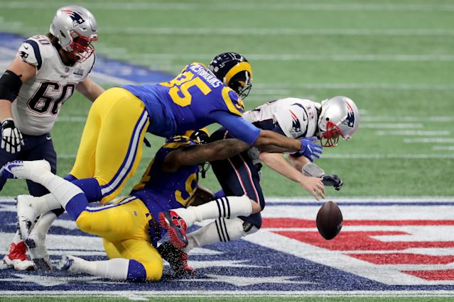 <p>Tom Brady #12 of the New England Patriots is sacked by Aaron Donald #99 and Ethan Westbrooks #95 of the Los Angeles Rams in the first half during Super Bowl LIII at Mercedes-Benz Stadium on February 3, 2019 in Atlanta, Georgia. (Photo by Elsa/Getty Images) </p>