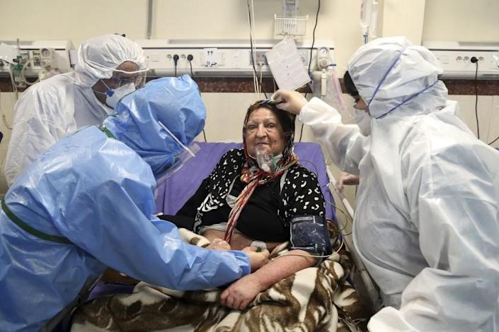 """A patient infected with the coronavirus is treated at a hospital in Tehran last month. Nine out of 10 cases of the virus in the Middle East come from the Islamic Republic and fears remain that Iran may be underreporting its cases. <span class=""""copyright"""">(Mohammad Ghadamali / Associated Press)</span>"""