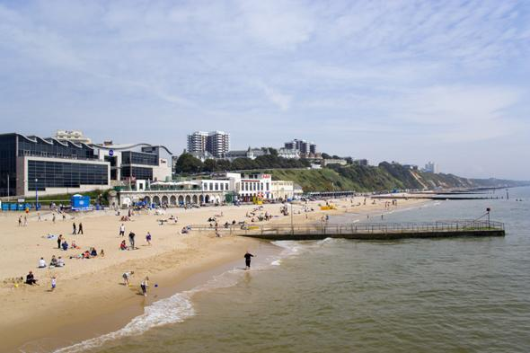 ENGLAND Dorset Bournemouth The East Beach showing the Imax Complex and seafront attractions with people on the beach and at the waters edge between the groynes. Clifftop hotels and flats in the distance