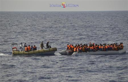 Migrants sit in boats during a rescue operation by Italian navy ship Cigala Fulgosi off the coast of the south of the Italian island of Sicily