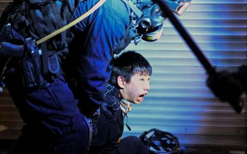 A pro-democracy protester is held by police outside Tsim Sha Tsui Police station during a demonstration - Credit: AFP