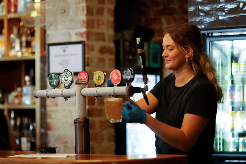 BUNBURY, AUSTRALIA - MAY 18: A Bartender pours a beer for their customers at the Rose Hotel in Bunbury on May 18, 2020 in Bunbury, Australia. COVID-19 restrictions have further eased across Western Australia in response to the state's declining infection rate. From Monday 18 May, restaurants and cafes can open for up to 20 patrons to dine in, while indoor and outdoor gatherings of up to 20 people are also permitted. Regional travel boundaries have also been eased, with temporary regional borders reduced from 13 to four. Travel is permitted within the Mid-West, Gascoyne and Pilbara, the Goldfields-Esperance region and within the Kimberley. While travel between South West, Great Southern, Wheatbelt and Peel regions to Perth is also now permitted.Travel between Perth and the other regions remains prohibited, and Western Australia's interstate border also remains closed. (Photo by James Worsfold/Getty Images)