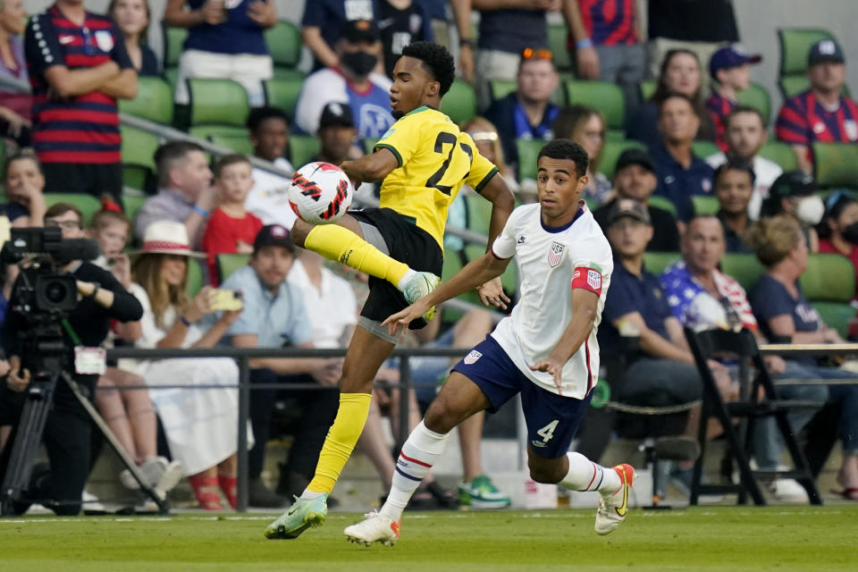 Jamaica's Tyreek Magee (21) and United States' Tyler Adams (4) compete for control of the ball during a FIFA World Cup qualifying soccer match, Thursday, Oct. 7, 2021, in Austin, Texas. (AP Photo/Eric Gay)