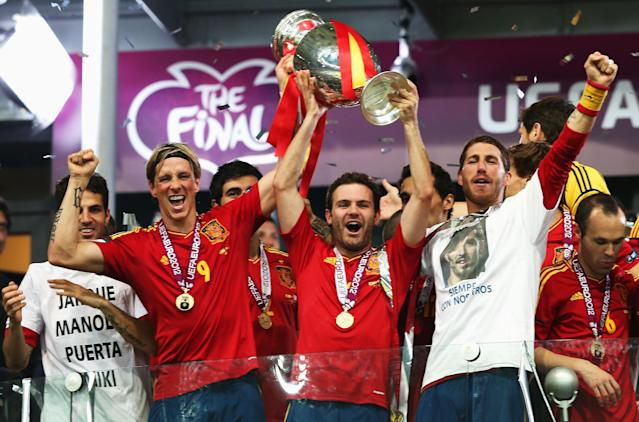 KIEV, UKRAINE - JULY 01: Goalscorers Fernando Torres and Juan Mata of Spain hold the trophy next to team-mates Cesc Fabregas and Sergio Ramos during the UEFA EURO 2012 final match between Spain and Italy at the Olympic Stadium on July 1, 2012 in Kiev, Ukraine. (Photo by Alex Grimm/Getty Images)
