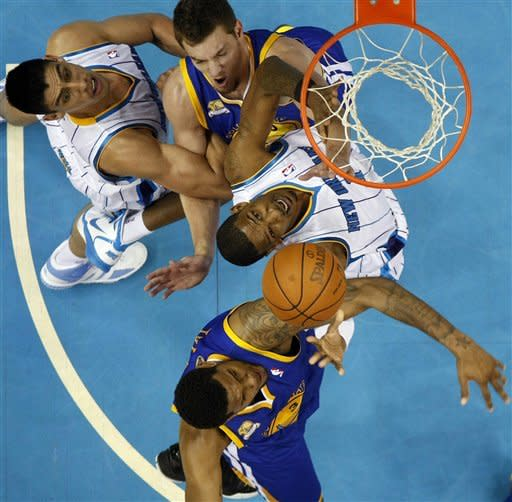 New Orleans Hornets forward Trevor Ariza, center, drives to the basket between Golden State Warriors' David Lee, top center, and Jeremy Tyler, bottom, as Hornets forward Gustavo Ayon (15), top left, blocks, during the first half of an NBA basketball game in New Orleans, Wednesday, March 21, 2012. (AP Photo/Gerald Herbert)