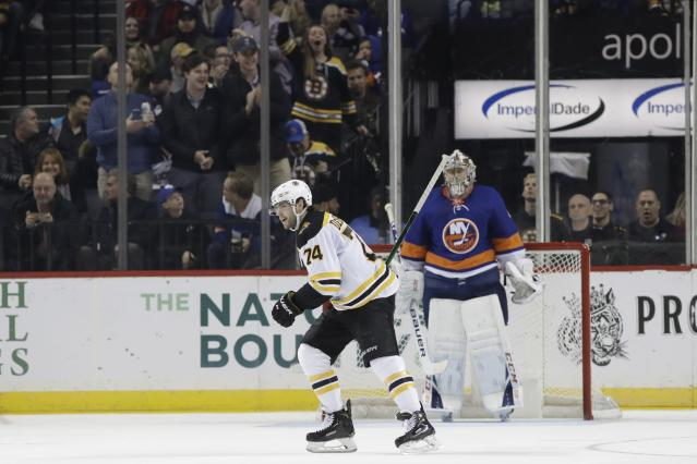 Boston Bruins fans cheer as Jake DeBrusk (74) skates past New York Islanders goaltender Semyon Varlamov (40) after scoring a goal during the second period of an NHL hockey game Saturday, Jan. 11, 2020, in New York. (AP Photo/Frank Franklin II)