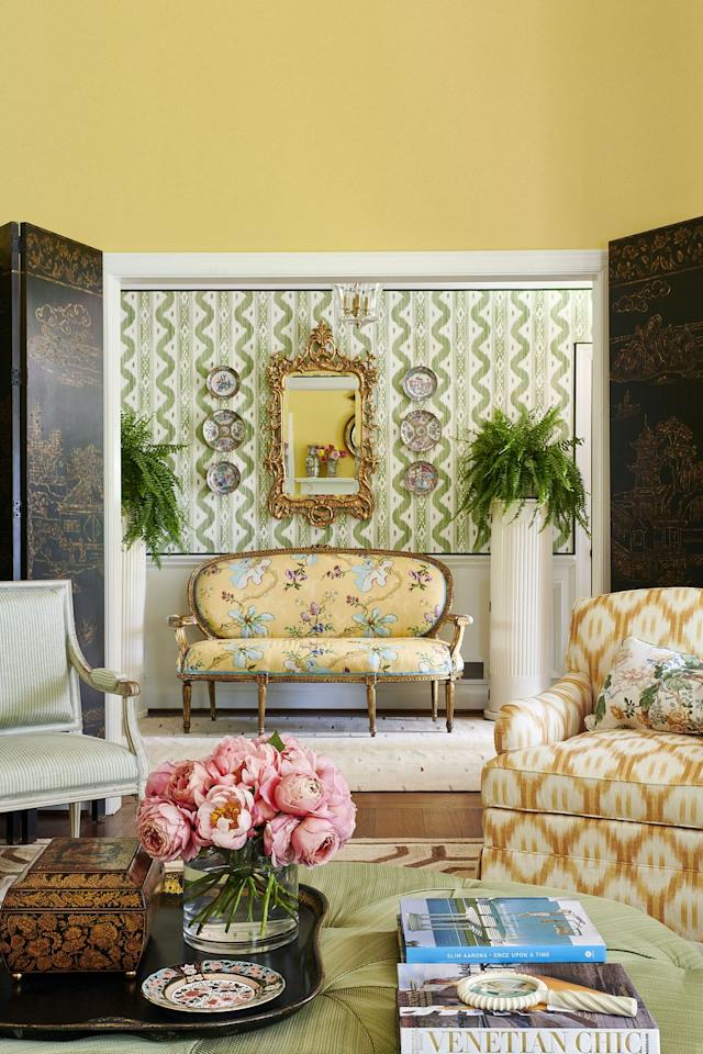 """<p>The use of color was important in decorating this Mountain Brook, Alabama, home. Designer <a href=""""https://markdsikes.com"""" target=""""_blank"""">Mark D. Sikes</a> painted the living room a sunny yellow, which is the perfect transition to a lovely green foyer. A <a href=""""http://quadrillefabrics.com"""" target=""""_blank"""">Quadrille</a> wallcovering and <a href=""""https://www.kravet.com/brunschwig-fils"""" target=""""_blank"""">Brunschwig & Fils</a> fabric play well together, and a grouping of china, a gilded mirror, and columns boasting ferns frame the settee as a charming resting place in the entryway. </p>"""