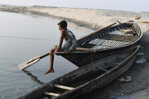 A boy sits on a boat in Barpeta village in Assam, where many residents were left off a newly compiled register of citizens