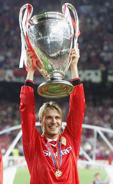 "FILE - This is a May 25, 1999 file photo of Manchester United's midfielder David Beckham holding the winner's cup, after his side defeated Bayern Munich in their Champions League final football match, at the Nou Camp stadium. David Beckham is retiring from soccer after the season, ending a career in which he become a global superstar since starting his career at Manchester United. The 38-year-old Englishman recently won a league title in a fourth country with Paris Saint-Germain. He said in a statement Thursday May 16, 2013 he is ""thankful to PSG for giving me the opportunity to continue but I feel now is the right time to finish my career, playing at the highest level."" (AP Photo/Phil Noble/PA, File) UNITED KINGDOM OUT"