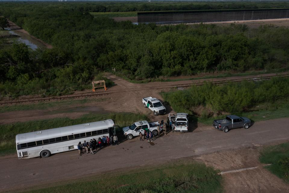 File image: Part of an incomplete border wall is seen in the background as asylum-seeking migrants from Central America line-up outside of a US board patrol bus after crossing the Rio Grande river into the United States from Mexico in La Joya, Texas, US, 20 May, 2021 (REUTERS)