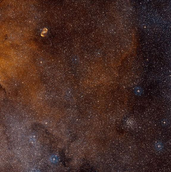 This wide-field view shows a region of sky in the southern constellation of Norma (The Carpenter's Square). At the centre lies the massive star-forming region SDC 335.579-0.292, but this is too obscured by dust to be visible. Image released Jul