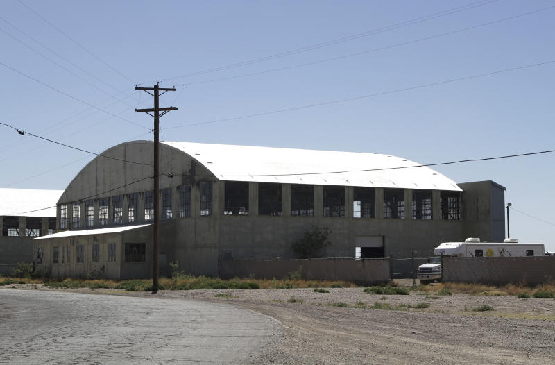 This Wednesday, May 22, 2019, photo shows a World War II-era bomber hanger in Deming, N.M. A surge of asylum-seeking families has been straining cities along the southern U.S. border for months, but now the issue is flowing into cities far from Mexico, where immigrants are being housed in an airplane hangar and rodeo fairgrounds and local authorities are struggling to keep up with the influx. (AP Photo/Cedar Attanasio)