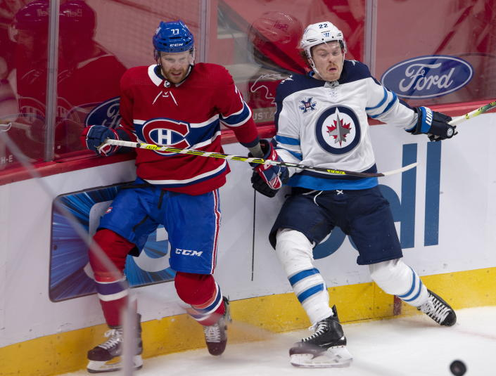 Montreal Canadiens' Brett Kulak (77) and Winnipeg Jets' Mason Appleton (22) go after a loose puck during the second period of an NHL hockey game, Thursday, April 8, 2021 in Montreal. (Ryan Remiorz/The Canadian Press via AP)