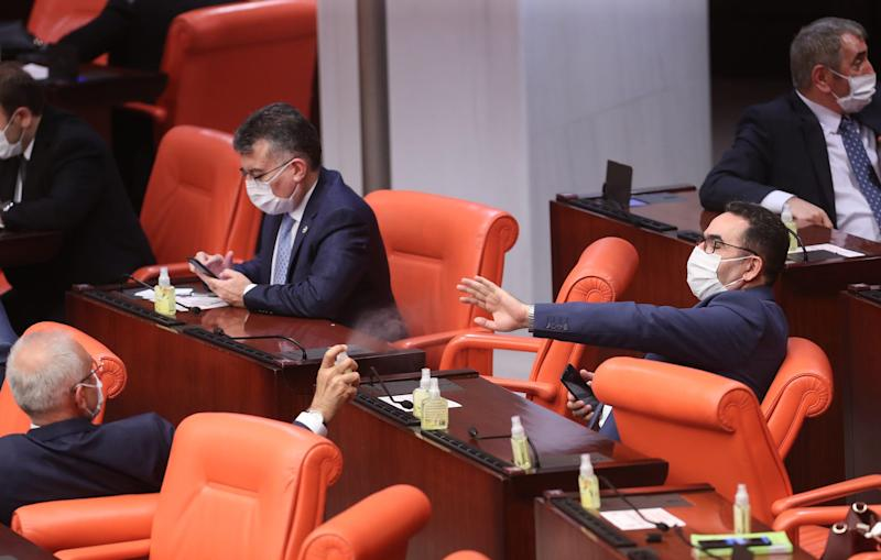 Turkish Members of Parliament wear protective facemasks and share disinfectant gel, as a precaution against the novel coronavirus, during the general assembly meeting of The Grand National Assembly of Turkey in Ankara on April 7.