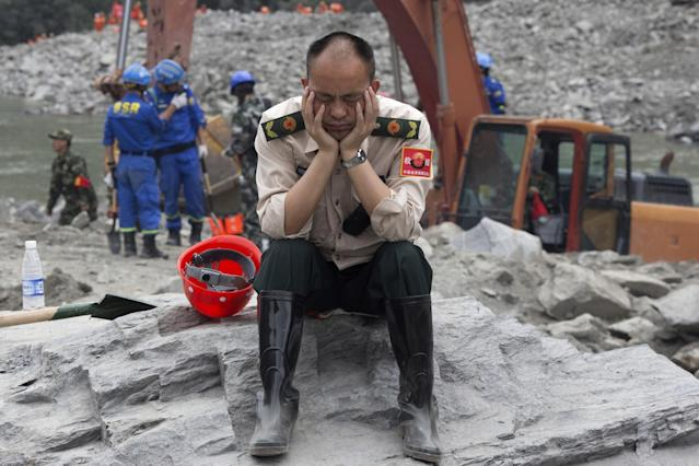 <p>A rescue worker takes a nap at the site of a landslide in Xinmo village in Maoxian County in southwestern China's Sichuan Province, Sunday, June 25, 2017. Crews searching through the rubble left by a landslide that buried a mountain village under tons of soil and rocks in southwestern China on Saturday found bodies, but more than 100 people remained missing. (Photo: Ng Han Guan/AP) </p>