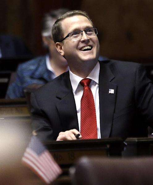 In this photo taken Wednesday, Feb. 20, 2013, Rep. Matt Shea, R-Spokane Valley, smiles as he sits at his desk on the House floor in Olympia, Wash. It has been just shy of 50 years since the U.S. Supreme Court ruled that a Washington state law barring members of the Communist Party from working for the state is unconstitutional. Evidently, that is not enough time to remove it from the books. Rep. Joe Fitzgibbon, D-Burien, first introduced a measure to repeal the anachronistic law last year, saying that it would be a quiet end to a moot statute originating from a dark period in our nation's history. Shea opposes the measure. (AP Photo/Elaine Thompson)
