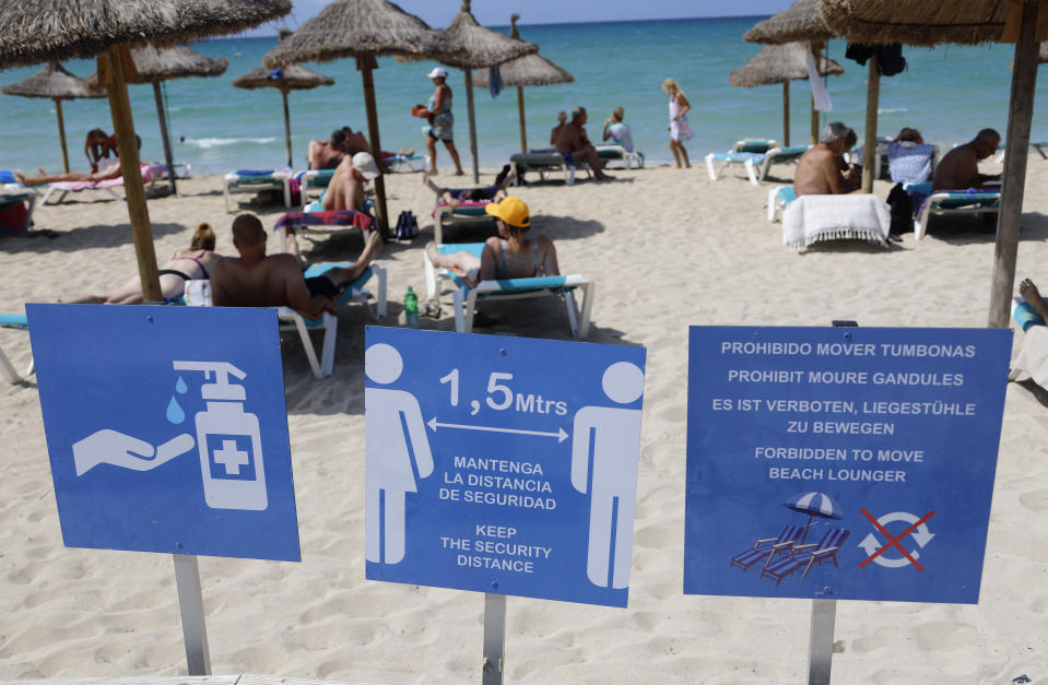15 August 2020, Spain, Palma: People sunbathe and swim on the beach of Arenal in Mallorca. In the foreground you can see a sign indicating the distance regulations. In view of the increased risk of infection, the German government has classified almost all of Spain, including Majorca, as a risk area. The classification means that returning holidaymakers are required to test for the coronavirus. Photo: Clara Margais/dpa (Photo by Clara Margais/picture alliance via Getty Images)