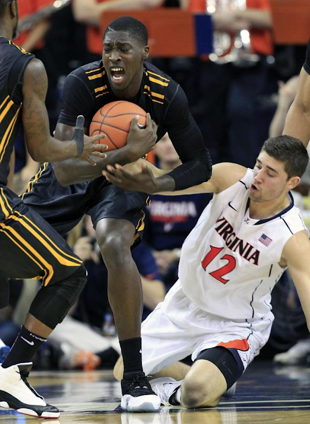 Virginia Commonwealth forward Jarred Guest, left, grabs a loose ball as Virginia guard Joe Harris (12) defends during the first half of an NCAA college basketball game in Charlottesville, Va., Tuesday, Nov. 12, 2013. (AP Photo/Steve Helber)