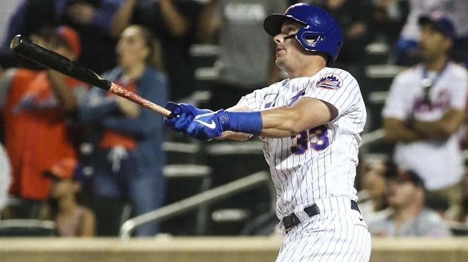 Jun 25, 2021; New York City, New York, USA; New York Mets pinch hitter James McCann (33) hits the game-tying sacrifice fly in the eighth inning against the Philadelphia Phillies at Citi Field