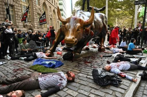 Protestors covered in fake blood gather around the Wall Street Bull during an ?Extinction Rebellion? demonstration in New York