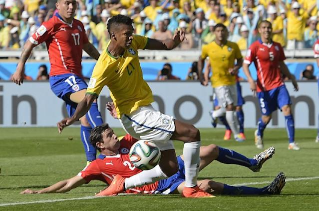 Brazil's Jo misses a pass and an opportunity to score while being defended by Chile's Eugenio Mena during the World Cup round of 16 soccer match between Brazil and Chile at the Mineirao Stadium in Belo Horizonte, Brazil, Saturday, June 28, 2014. (AP Photo/Manu Fernandez)