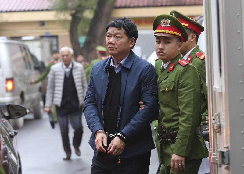 FILE - In this Monday, Jan. 8, 2018, file photo, Dinh La Thang is led to court by police in Hanoi, Vietnam. Prosecutors on Thursday recommended 14-15 years in prison for former Politburo member Dinh La Thang, an ex-chairman of state-owned energy giant PetroVietnam, on charges of violating management regulations. (Doan Tan/ Vietnam News Agency via AP, File)
