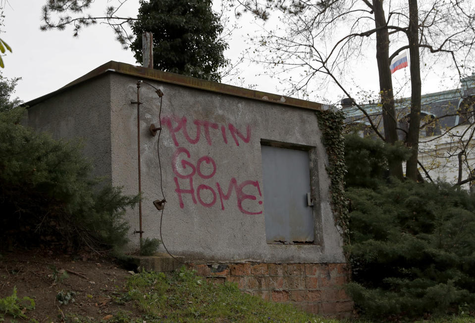A sign is painted on the wall by the Russian Embassy in Prague, Czech Republic, Thursday, April 22, 2021. The Czech Republic on Thursday ordered more Russian diplomats to leave the country, further escalating a fierce tug-of-war between the two nations over the alleged involvement of Russian spies in a massive ammunition depot explosion in 2014. (AP Photo/Petr David Josek)