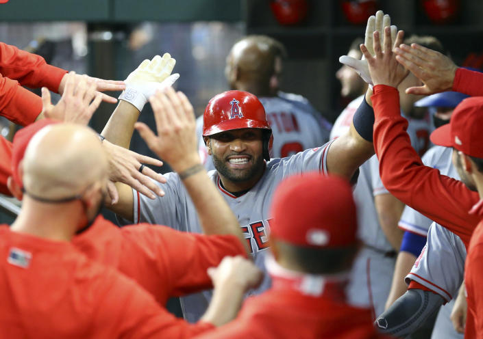 Los Angeles Angels first baseman Albert Pujols (5) is greeted in the dugout after a solo home run against the Texas Rangers in the third inning during a baseball game on Monday, April 26, 2021, in Arlington, Texas. (AP Photo/Richard W. Rodriguez)