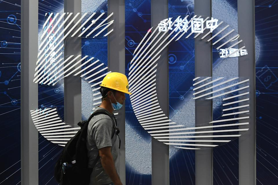 GUANGZHOU, CHINA - NOVEMBER 25: A man walks past a 5G sign before the 2020 World 5G Convention at Nan Fung International Convention & Exhibition Center on November 25, 2020 in Guangzhou, Guangdong Province of China. The 2020 World 5G Convention will be held on November 26-28 in Guangzhou. (Photo by VCG/VCG via Getty Images)