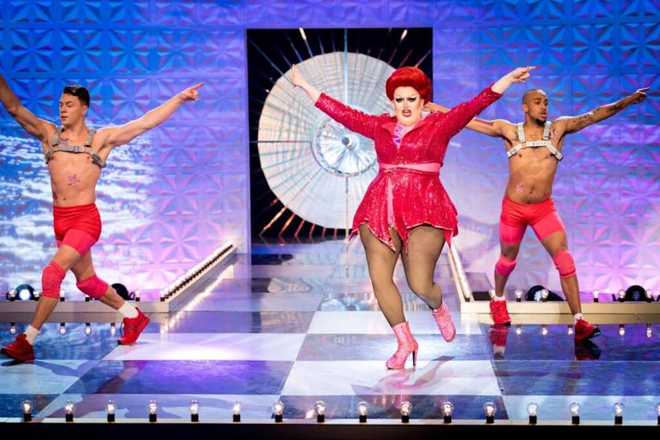 Drag queen Lawrence Chaney in a short, sparkly dress mid-dance mov, flanked by two male dancers in pink shorts and grey harnesses