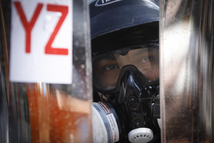 Protesters wearing helmet and gas mask take positions behind a makeshift barricade as armed riot policemen gather in Yangon, Myanmar, Monday, March 8, 2021. Myanmar security forces continued to clamp down on anti-coup protesters, firing tear gas to break up a crowd of around 1,000 people who were demonstrating in the capital, Naypyitaw. The protesters deployed fire extinguishers to create a smoke screen as they fled from authorities.(AP Photo)