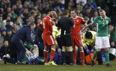 Football Soccer - Republic of Ireland v Wales - 2018 World Cup Qualifying European Zone - Group D - Aviva Stadium, Dublin, Republic of Ireland - 24/3/17 Wales' Gareth Bale and Ashley Williams with referee Nicola Rizzoli as Republic of Ireland's Seamus Coleman receives medical attention Action Images via Reuters / Matthew Childs Livepic