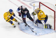 Sweden goalie Jesper Wallstedt (1) makes a save on United States' Landon Slaggert (26) as Victor Soderstrom (8) defends during the second period of an IIHF World Junior Hockey Championship game Thursday, Dec. 31, 2020, in Edmonton, Alberta. (Jason Franson/The Canadian Press via AP)