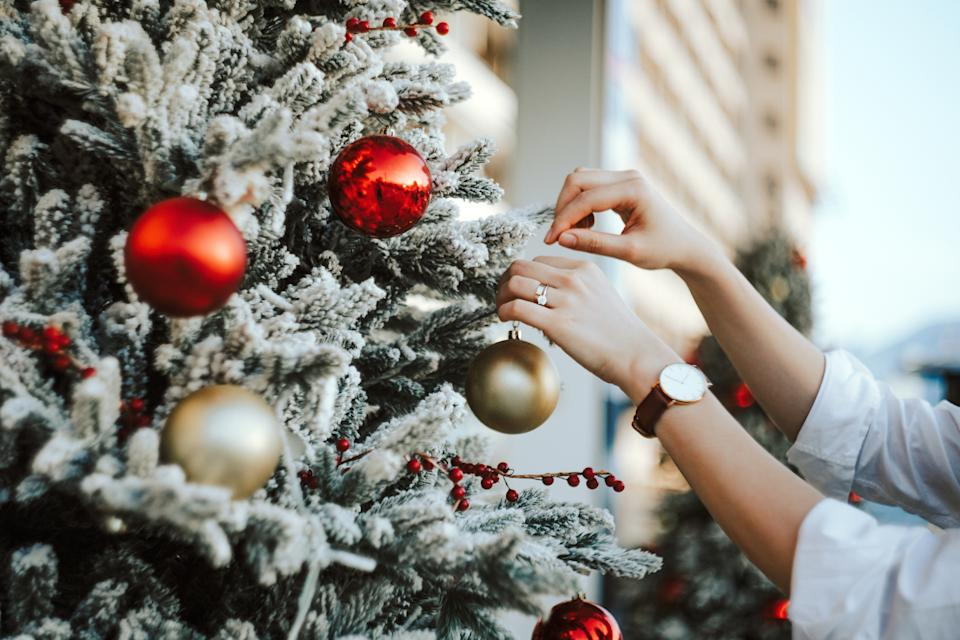 Woman putting baubles on a Christmas tree
