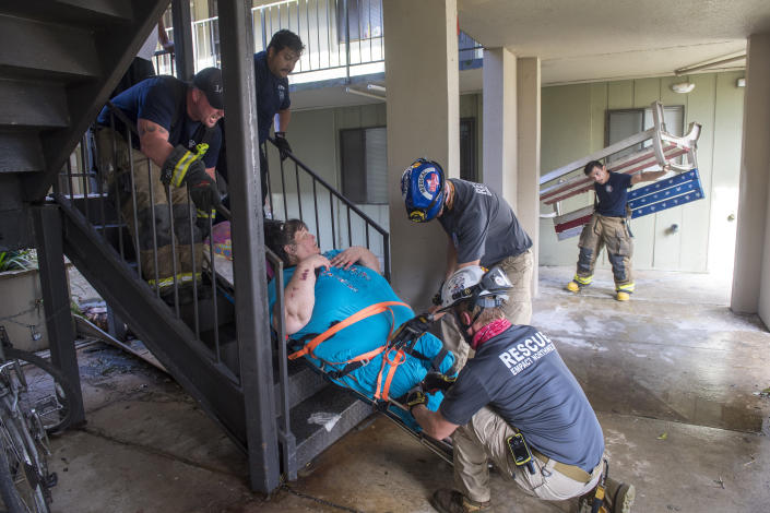 An American flag bench, right, was brought out to potentially use as a stretcher for a woman, top center, that was being rescued from the third floor of an apartment complex damaged by Hurricane Laura, as members of the fire department, the Cajun Navy, Empact Northwest, and other search and rescue teams helped the efforts on Friday, Aug. 28, 2020, in Lake Charles, La. Because of no electricity, residents of the complex were told they had to move out by the end of the day due. Some of the residents were not able to go down the stairs. (Chris Granger/The Advocate via AP)