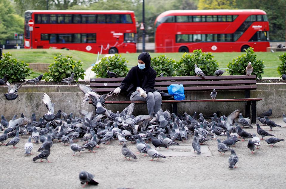"A woman wearing PPE (personal protective equipment), of a face mask and gloves as a precautionary measure against COVID-19, feeds pigeons in an almost deserted Marble Arch tourism site, in London on April 27, 2020, as tourists stay away due to the COVID-19 pandemic. - Prime Minister Boris Johnson on Monday made his first public appearance since being hospitalised with coronavirus three weeks ago, saying Britain was beginning to ""turn the tide"" on the outbreak but rejecting calls to ease a nationwide lockdown. (Photo by Tolga AKMEN / AFP) (Photo by TOLGA AKMEN/AFP via Getty Images)"